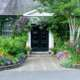 A sensory garden surrounds both sides of a traditional style black front door.